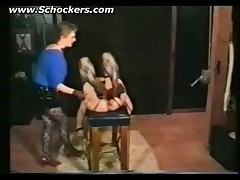 Dominatrix hits hot slave who is tied to a table in a dungeon on her ass and pussy with a stick bdsm